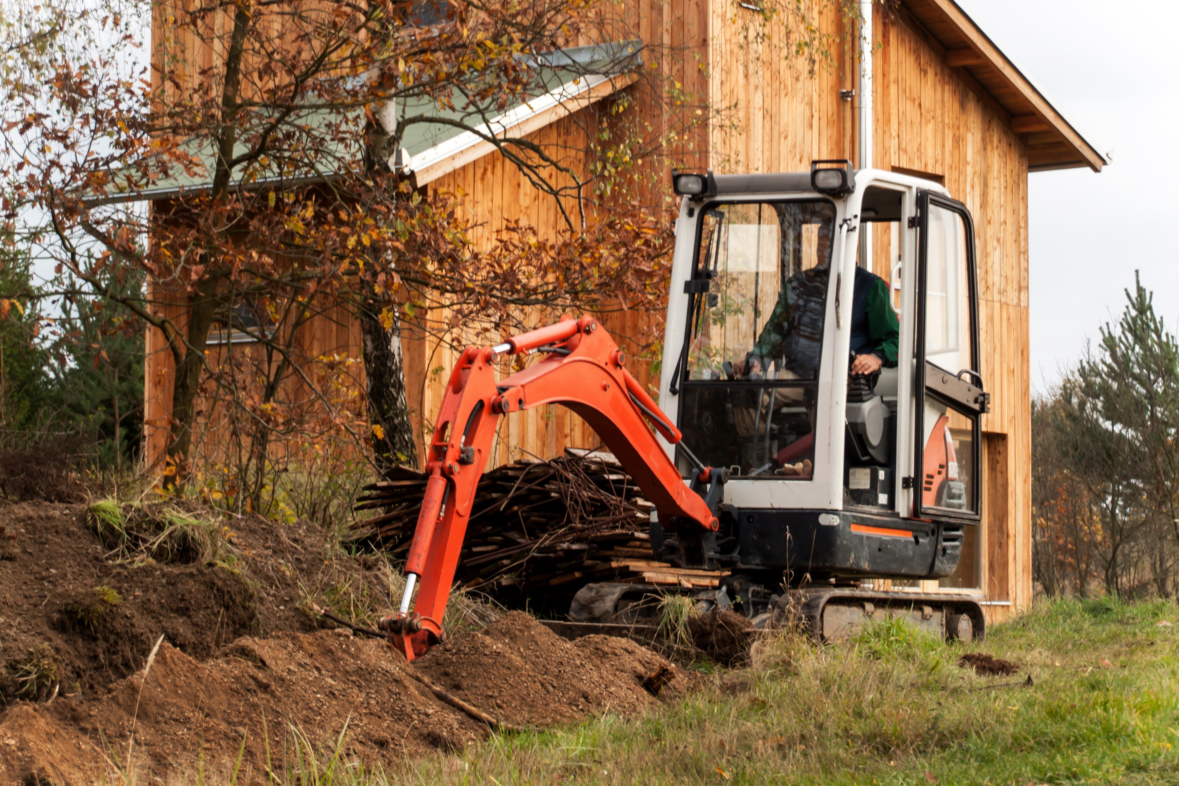 Mini excavator on construction site. Construction of a family house near a forest.